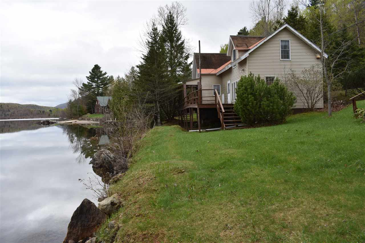 **Reduced by $23,000.**  The house with three gables possess a beautiful 216' of owned sandy bottom waterfront perfect for swimming or sunbathing. Go right from the deck to the beach with no time to spare.Home faces directly to the lake and enjoys the many sunrises and the water's glimmer.No more painting every summer, it's vinyl sided adding more time for fishing, boating or swimming. Over size 2 car garage for storage of anything you need. Bunk house has room for added quests. Driveway is paved so no muddy feet tracking through either. This was once a cottage and added onto each side as more room was needed. Cottage charm in the one section that reminds one of days at the lake without a care. Large living room downstairs looks right at the lake and can host many a gathering with lots of people. Deck provides outdoor BBQ and entertaining as well.  Reasonable offers considered.