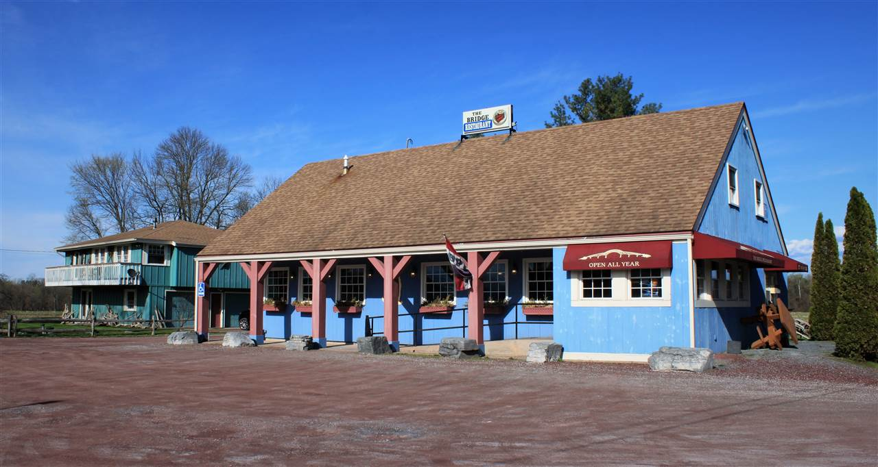The Bridge Restaurant For Sale! Long standing, successful, turn-key restaurant situated on a one of kind corner lot on the banks of Lake Champlain. Located at the corner of VT Routes 17 and 125 just steps from the Lake Champlain Bridge, the restaurant benefits from a traffic count of over 4,100 vehicles per day. Sale includes, business, land, commercial real estate, and single family home. Business sale includes all business assets: trade name, restaurant equipment, fixtures & furniture, url, recipes, goodwill. Commercial real estate is a 2,031 sf building, with 40 seat capacity, full commercial kitchen, take out window, central heating and cooling, covered porch, license for beer & wine sales. Single family home is a 1,690 sf, 1 or 2 bedroom house (currently configured as a 1 BR) that was built in 1978 but has been updated throughout over the past 5-10 years, includes: 2 car garage, front and rear decks, and a hot tub!
