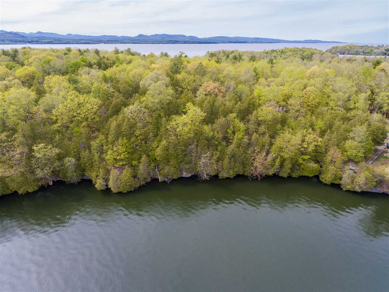 Beautiful Southeast facing parcel with 287 feet of lakeshore and lake access.  Excellent opportunity to build your year round dream home on Lake Champlain.  1970s camp on property with existing detached garage. Dave Marshall from Civil Engineering Associates did the site work and it's approved for 2 bedroom septic.