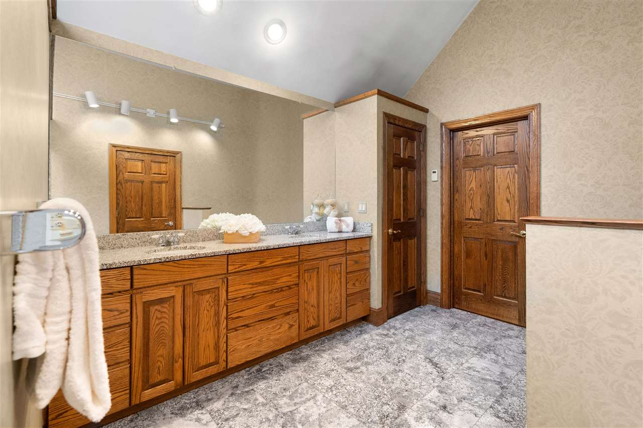 The oversized master bathroom features vaulted ceilings, granite & double vanity 14837634